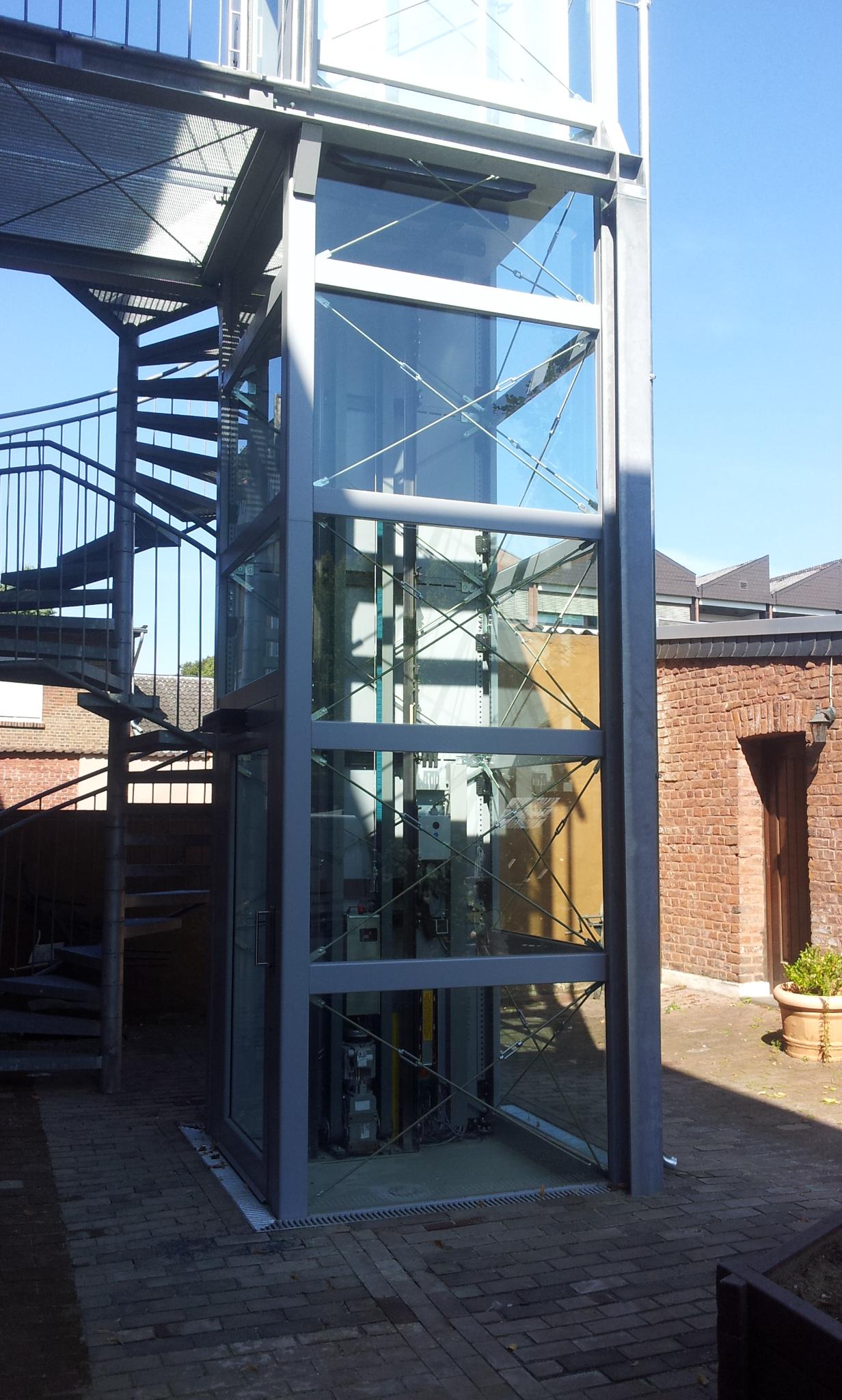 Glasaufzug neben Wendeltreppe