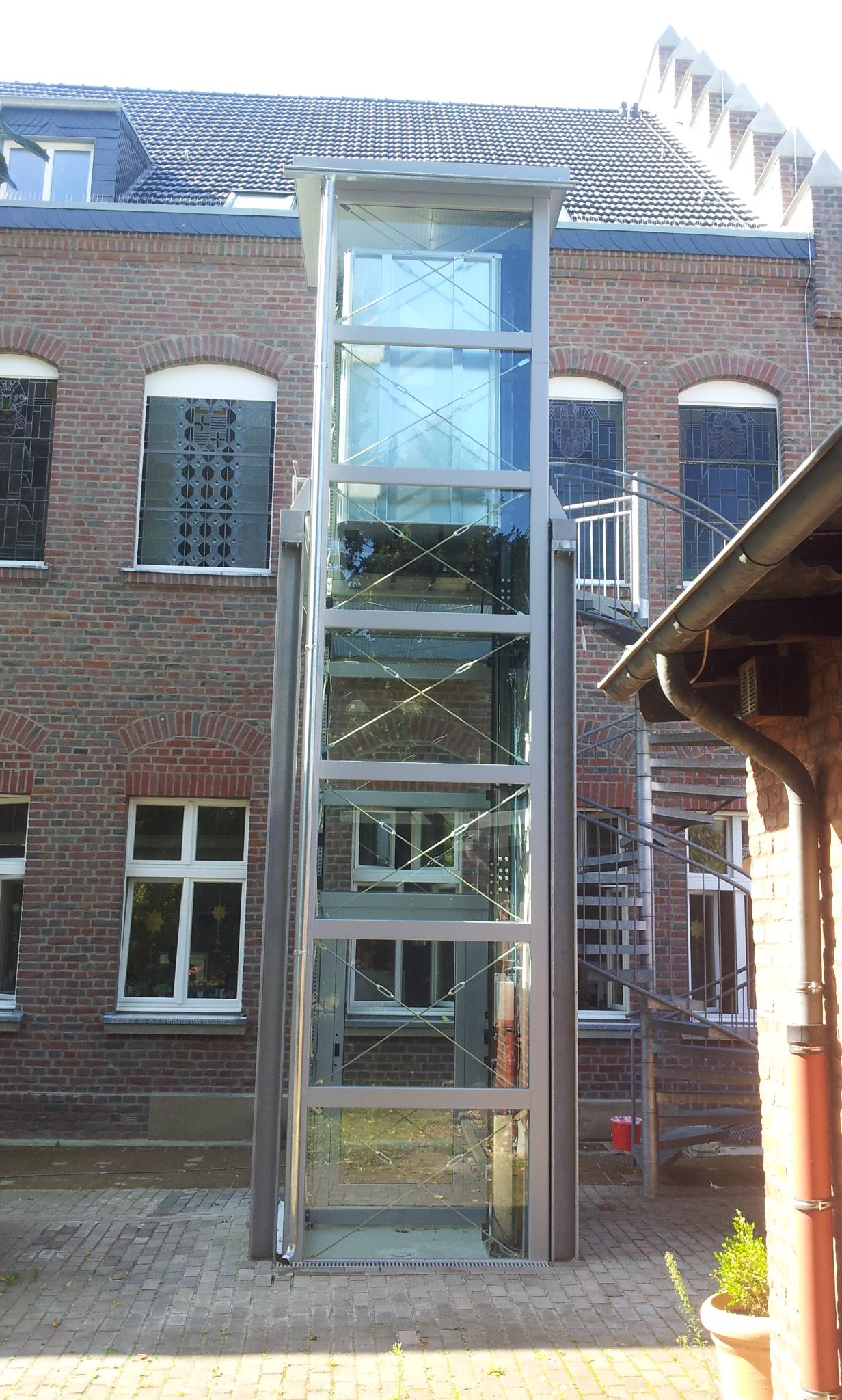 Glasaufzug vor Backsteingebäude