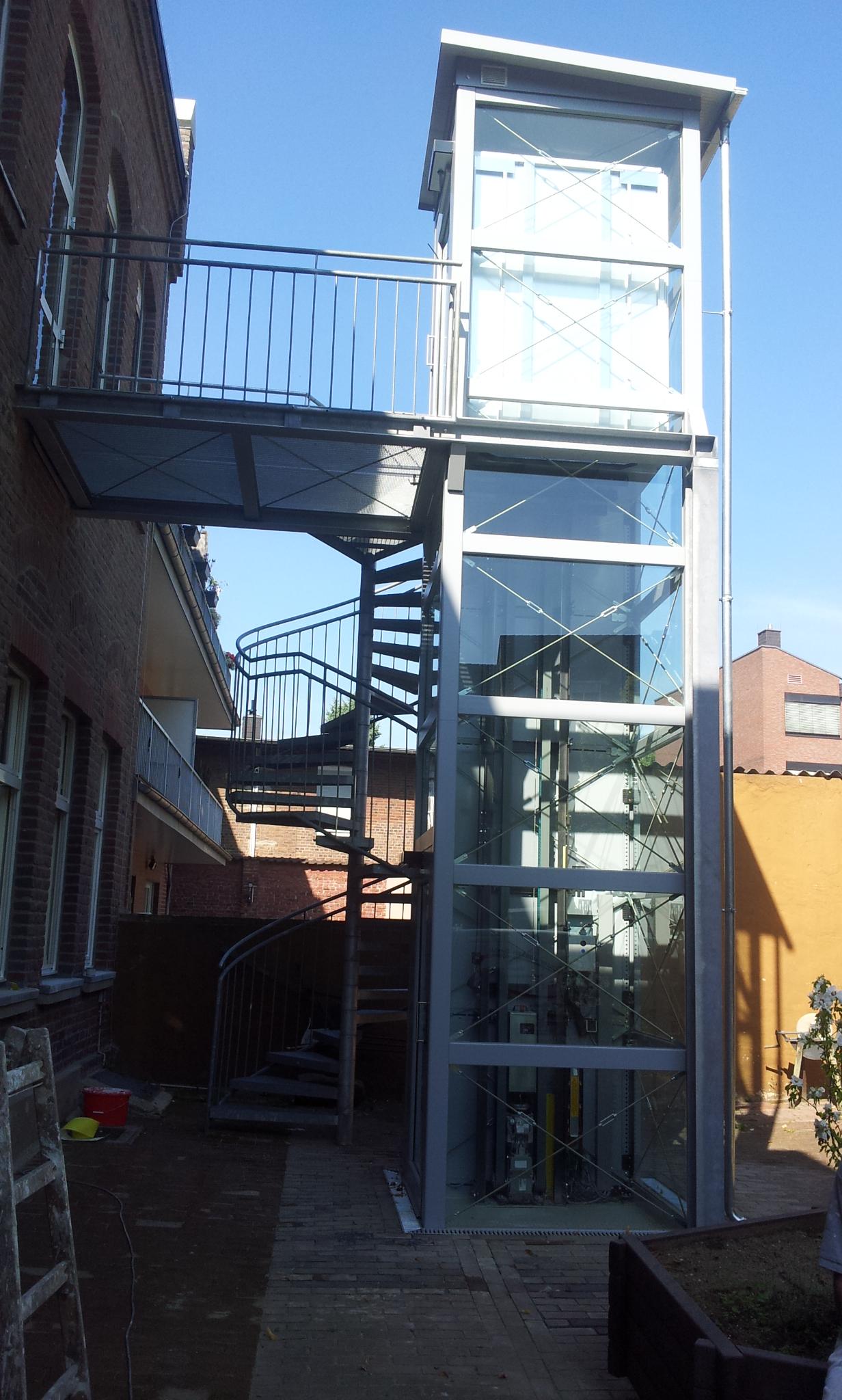 Glasaufzug mit Brücke oben als Zugang