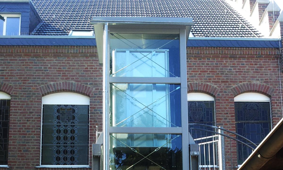 Glaslift außen an Backsteingebäude