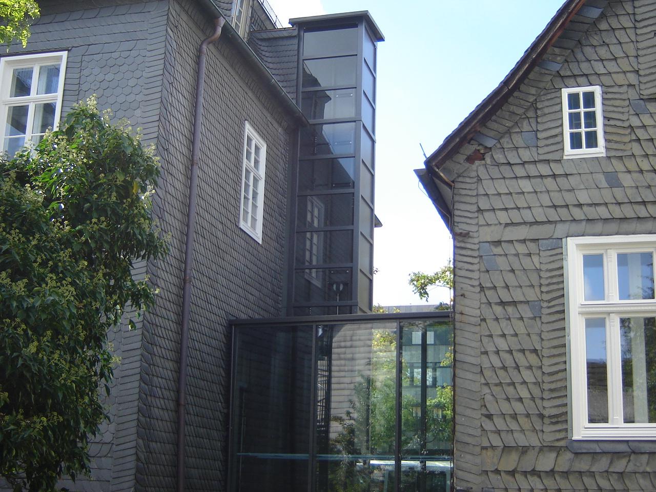 Außenaufzug installiert zwischen zwei schindelgedeckten Häusern