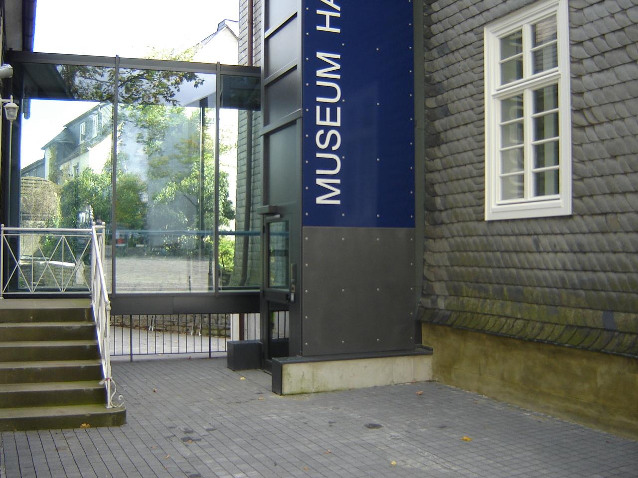 Außenaufzug neben einem schindelgedecktem Museumsbau