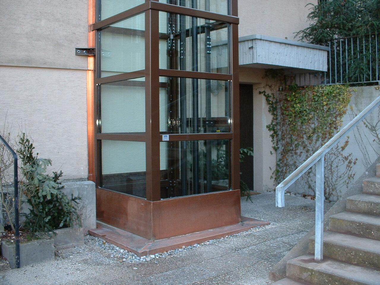Zugang zu gläsernem Aufzug außen im Hof
