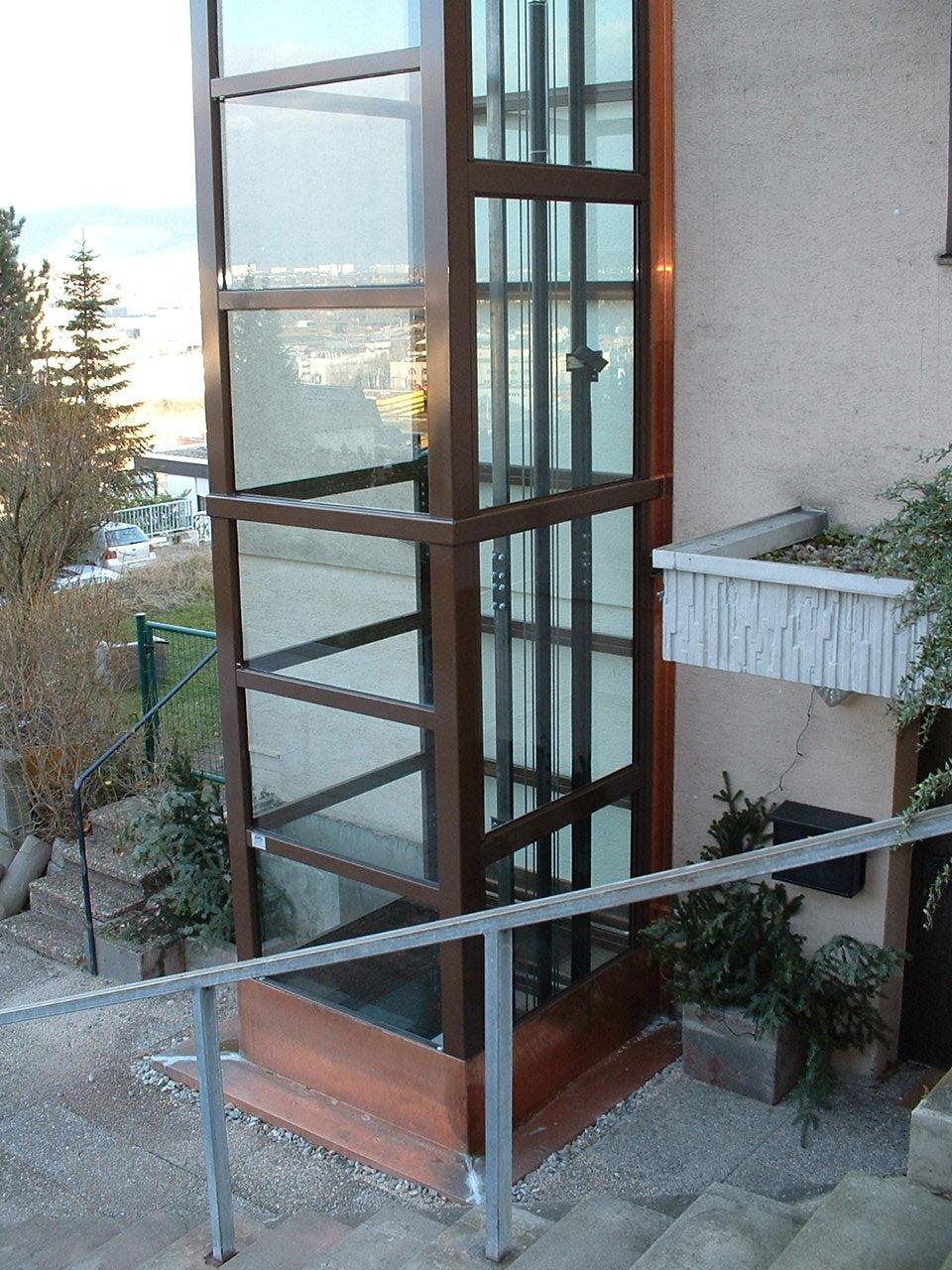 Gläserner Aufzug in Holzoptik außen