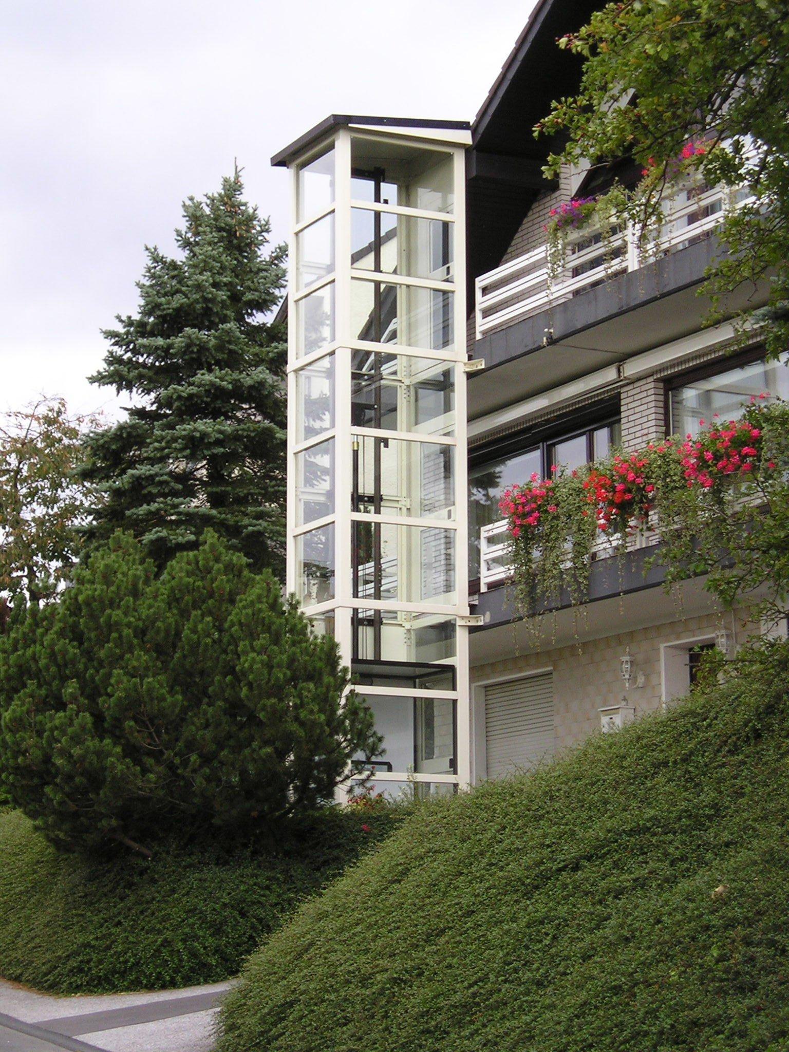 Glasaufzug weiß mit Zugang zu Balkonen bei mehrstöckigem Haus