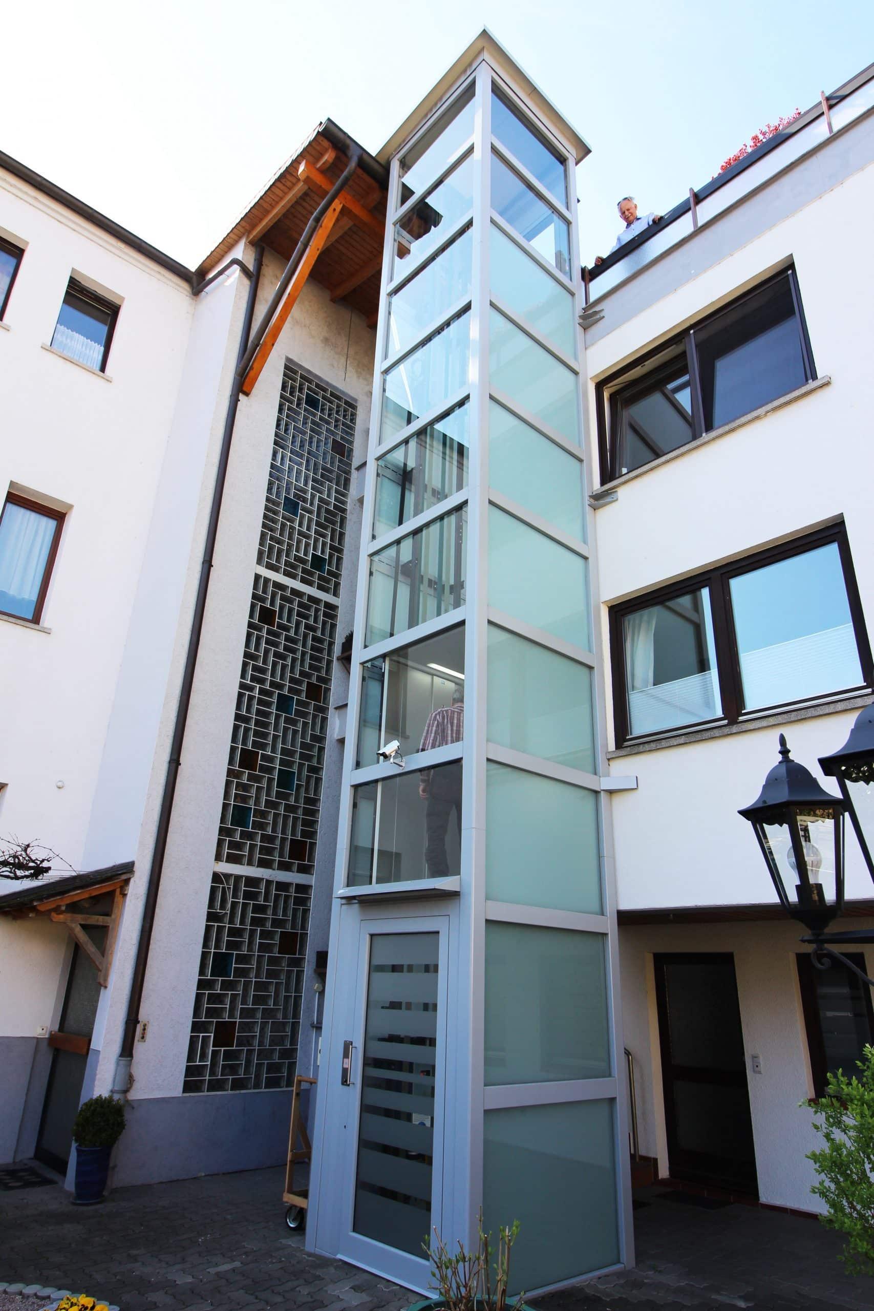 Außenlift aus Glas im Innenhof installiert