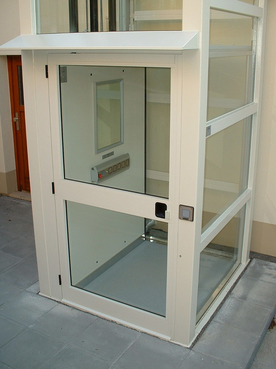 Außenaufzug aus Glas unten beim Zugang