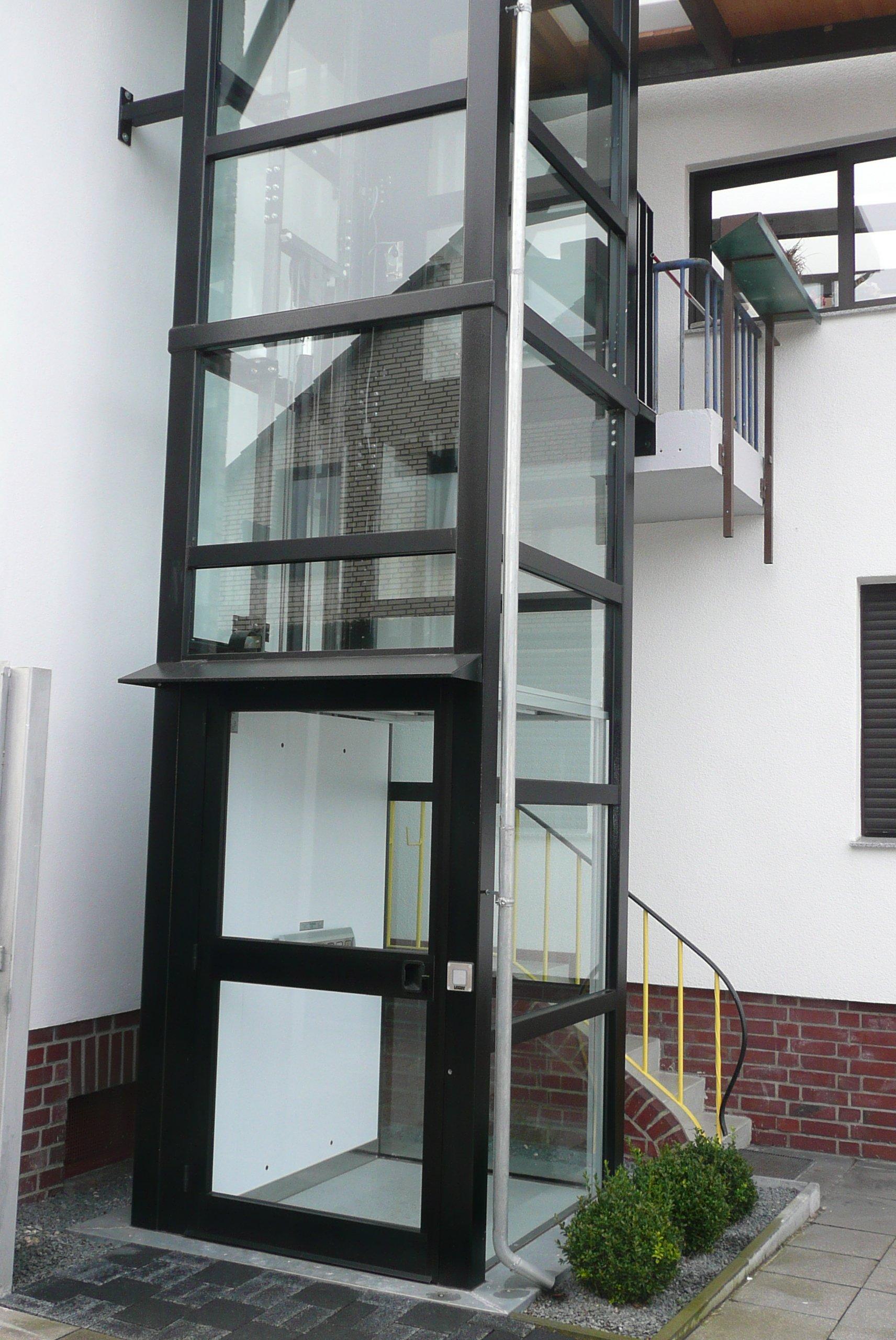 Außenaufzug, für den im 1. Stock ein Balkonzugang genutzt wird.