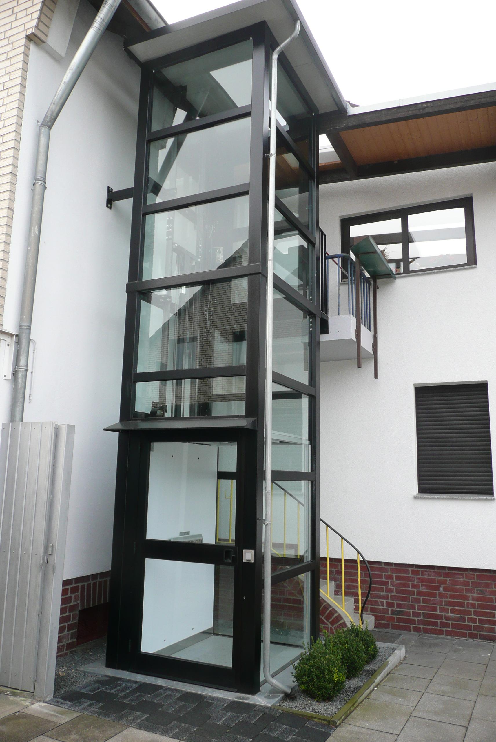 Außenaufzug aus Glas neben zweistöckigem Haus
