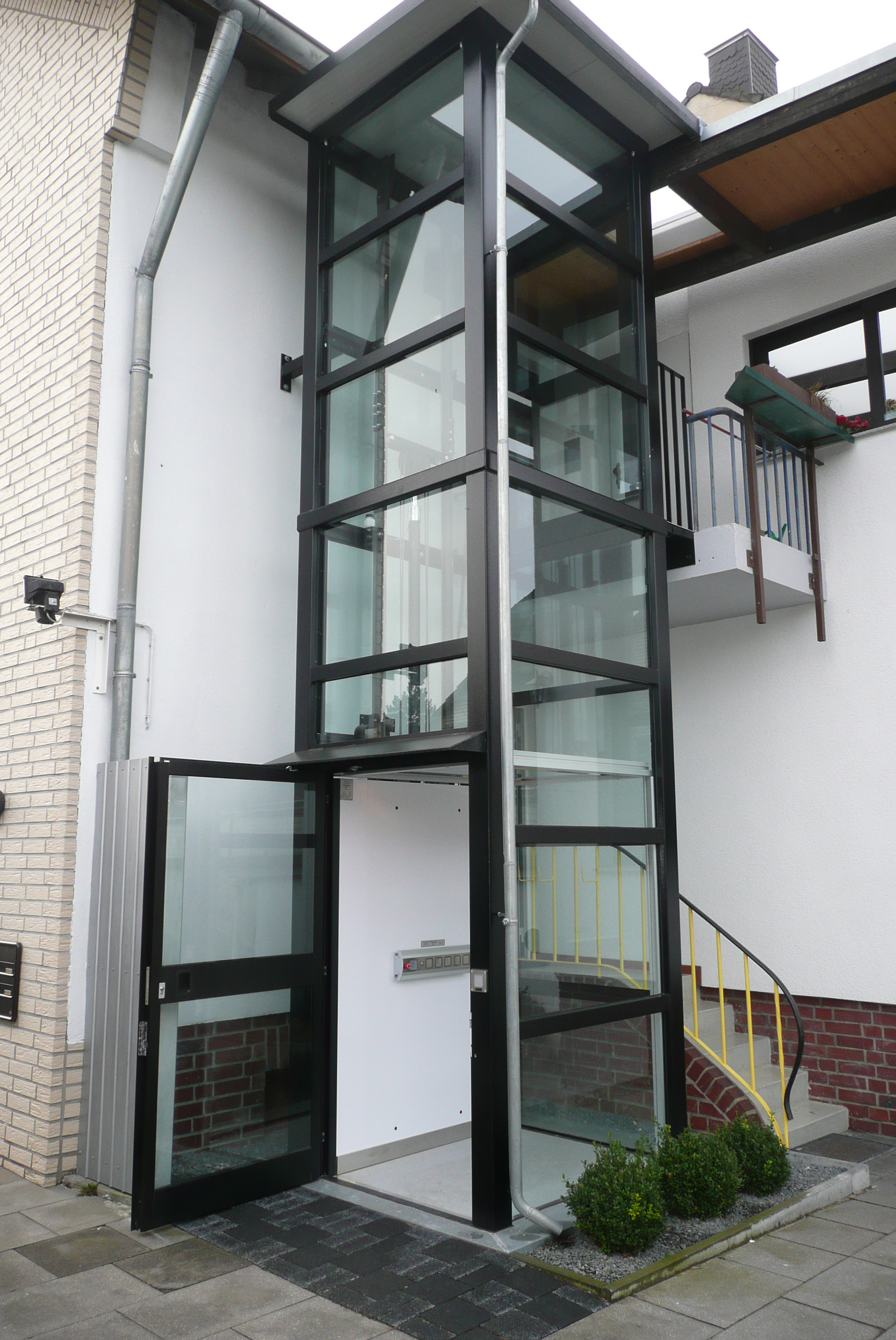 Außenaufzug mit Zugang über eine Art Balkon im 1. Stock