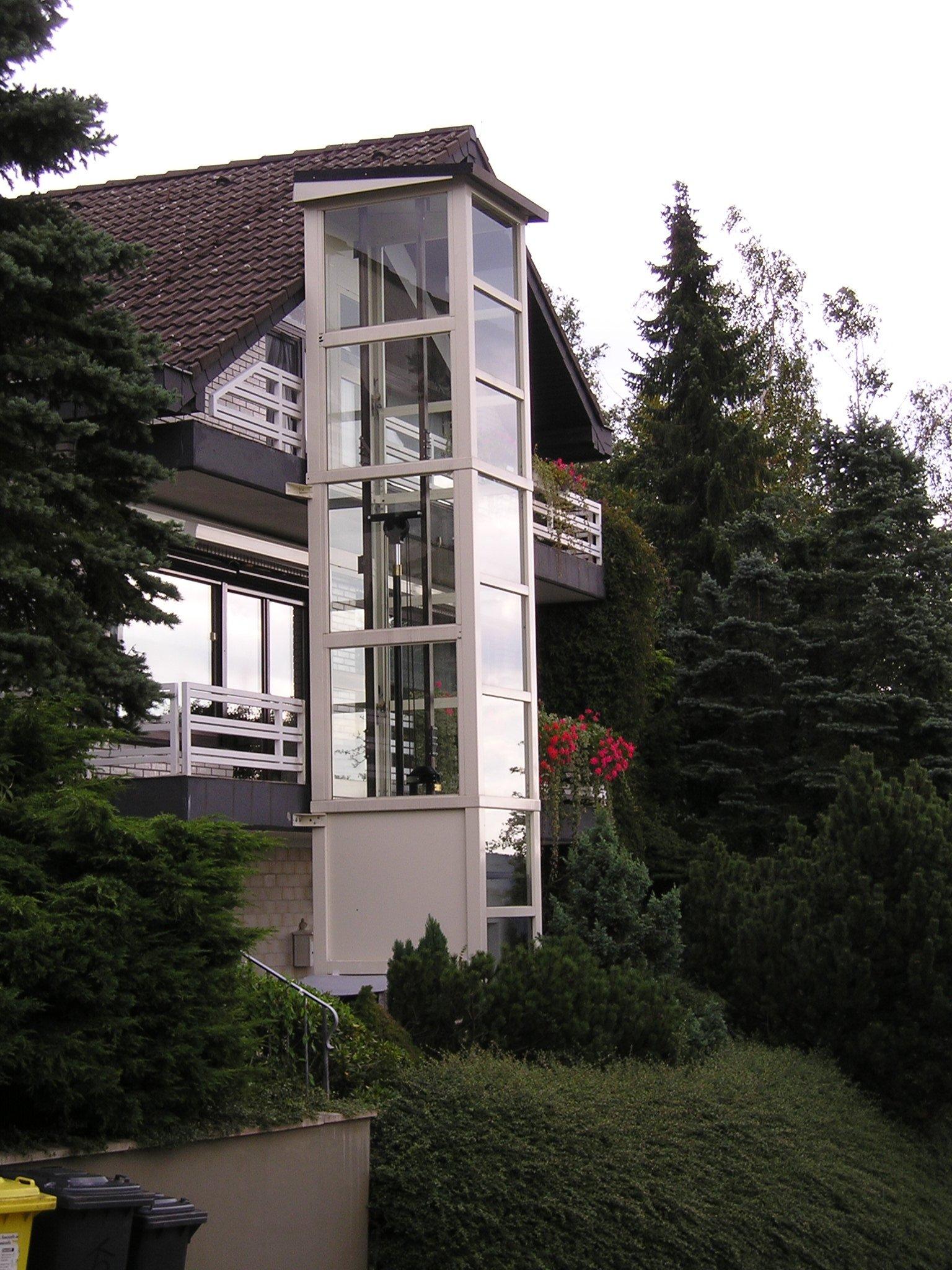 Glasaufzug außen neben Einfamilienhaus