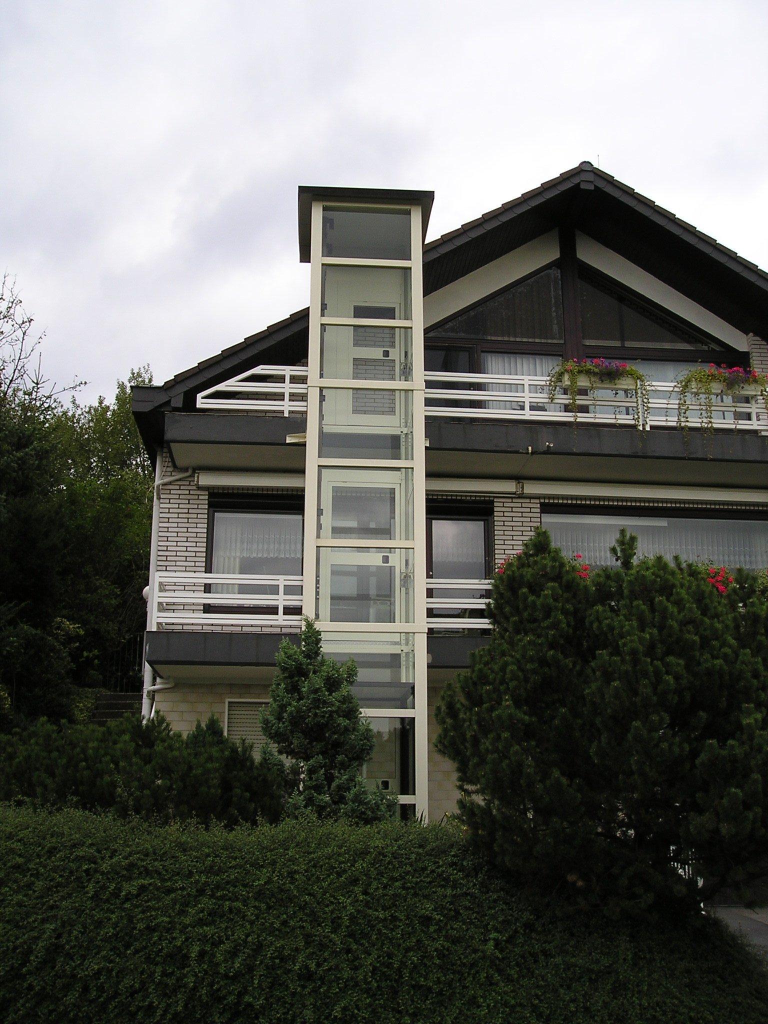 Weißer Glasaufzug bis ins Dachgeschoss eines Hauses
