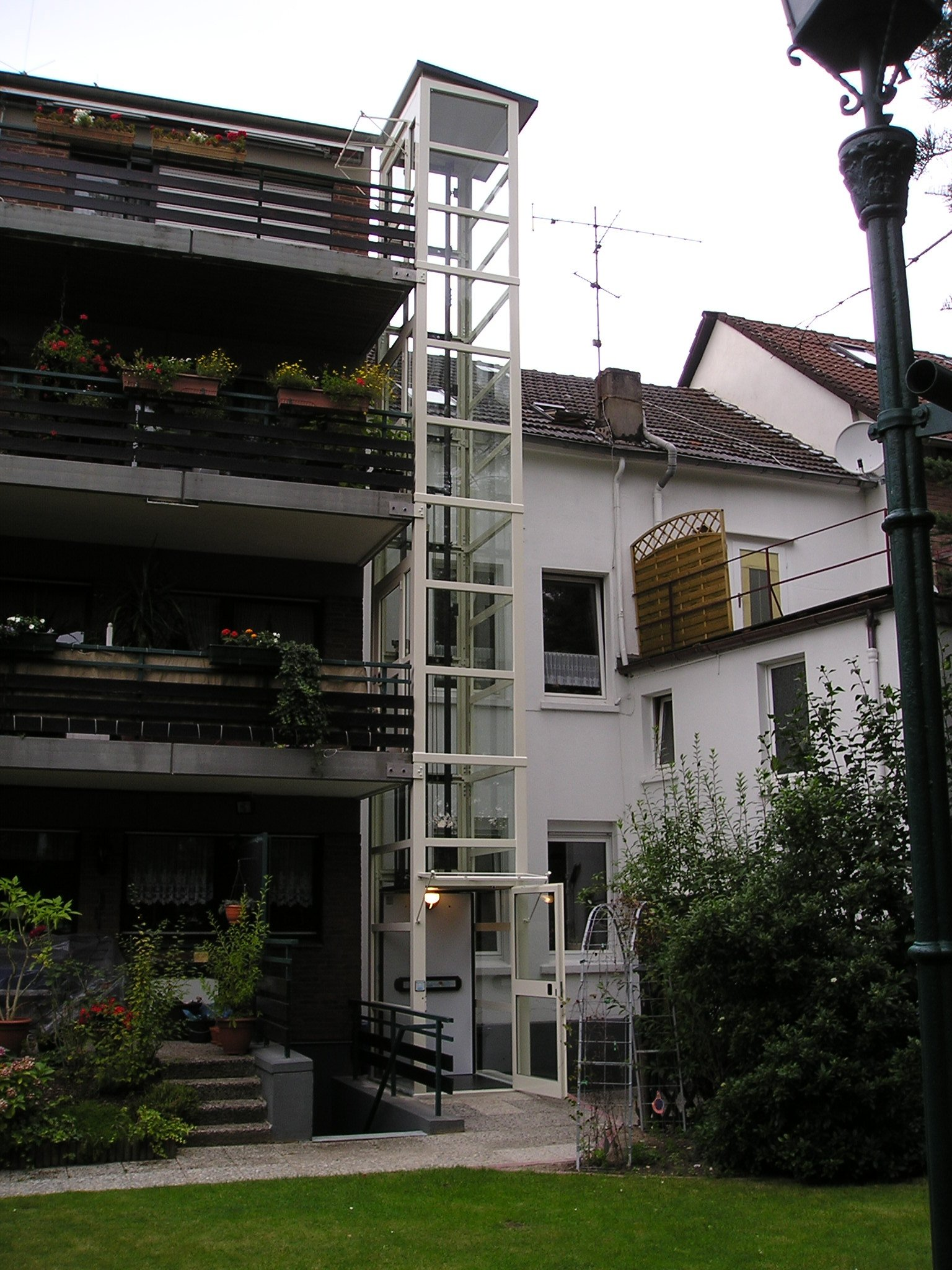 Weißer Glasaufzug neben Balkonen installiert