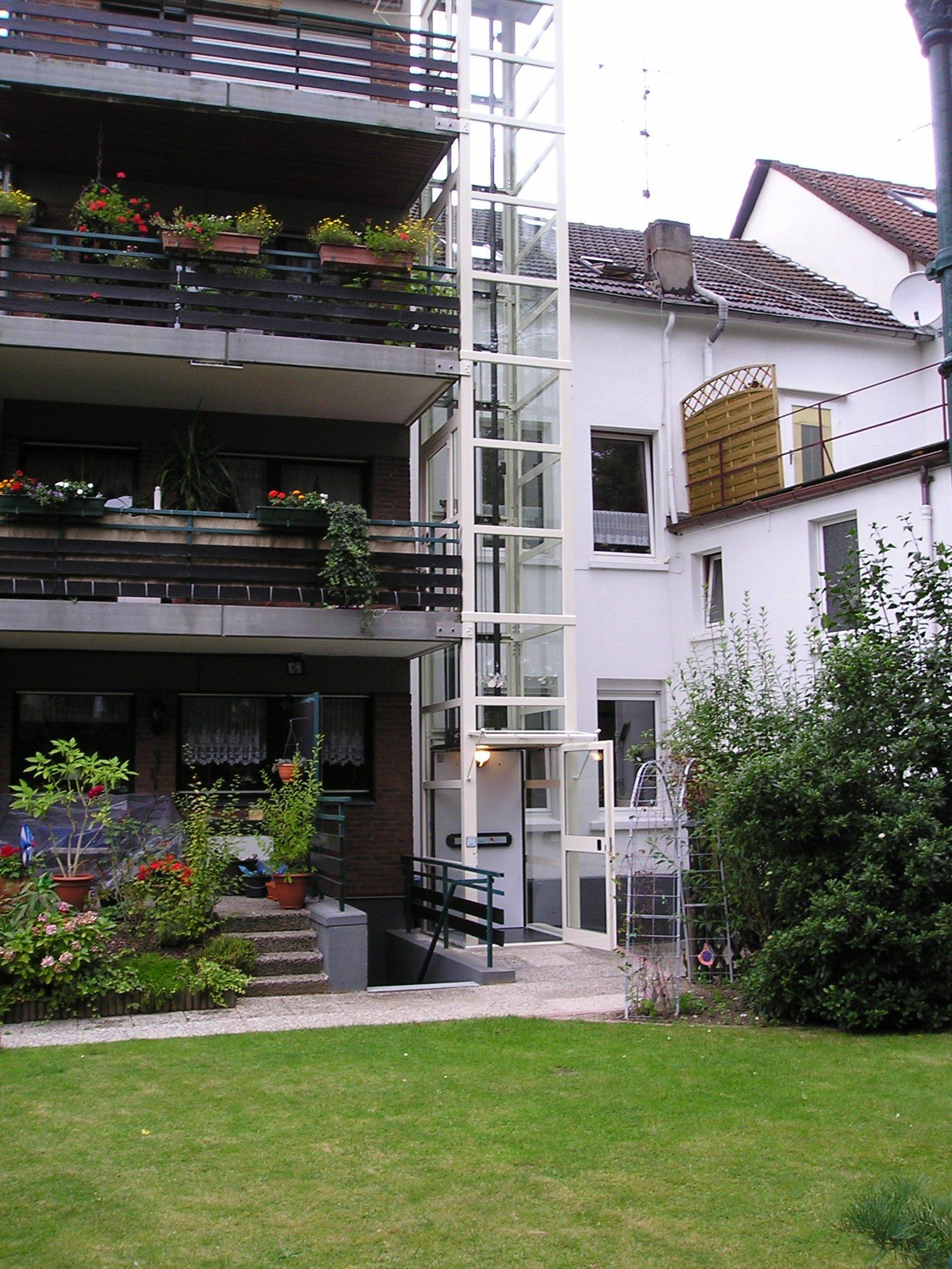 Glasaufzug mit Zugang über Balkone