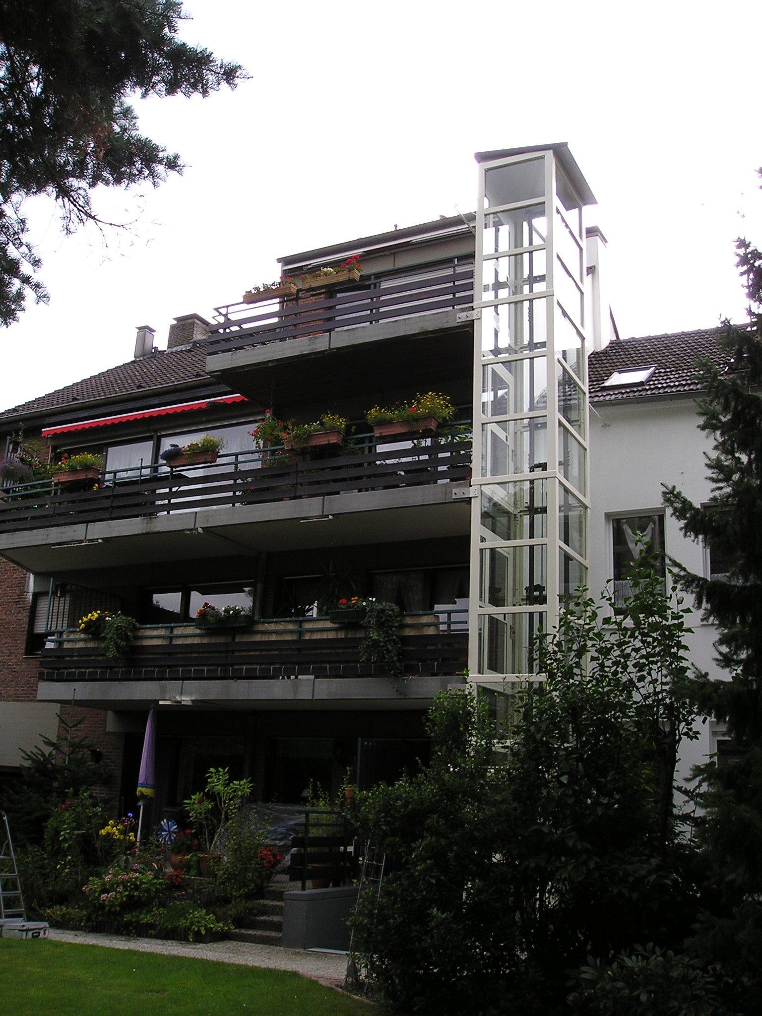 Gläserner Außenaufzug neben Balkonen