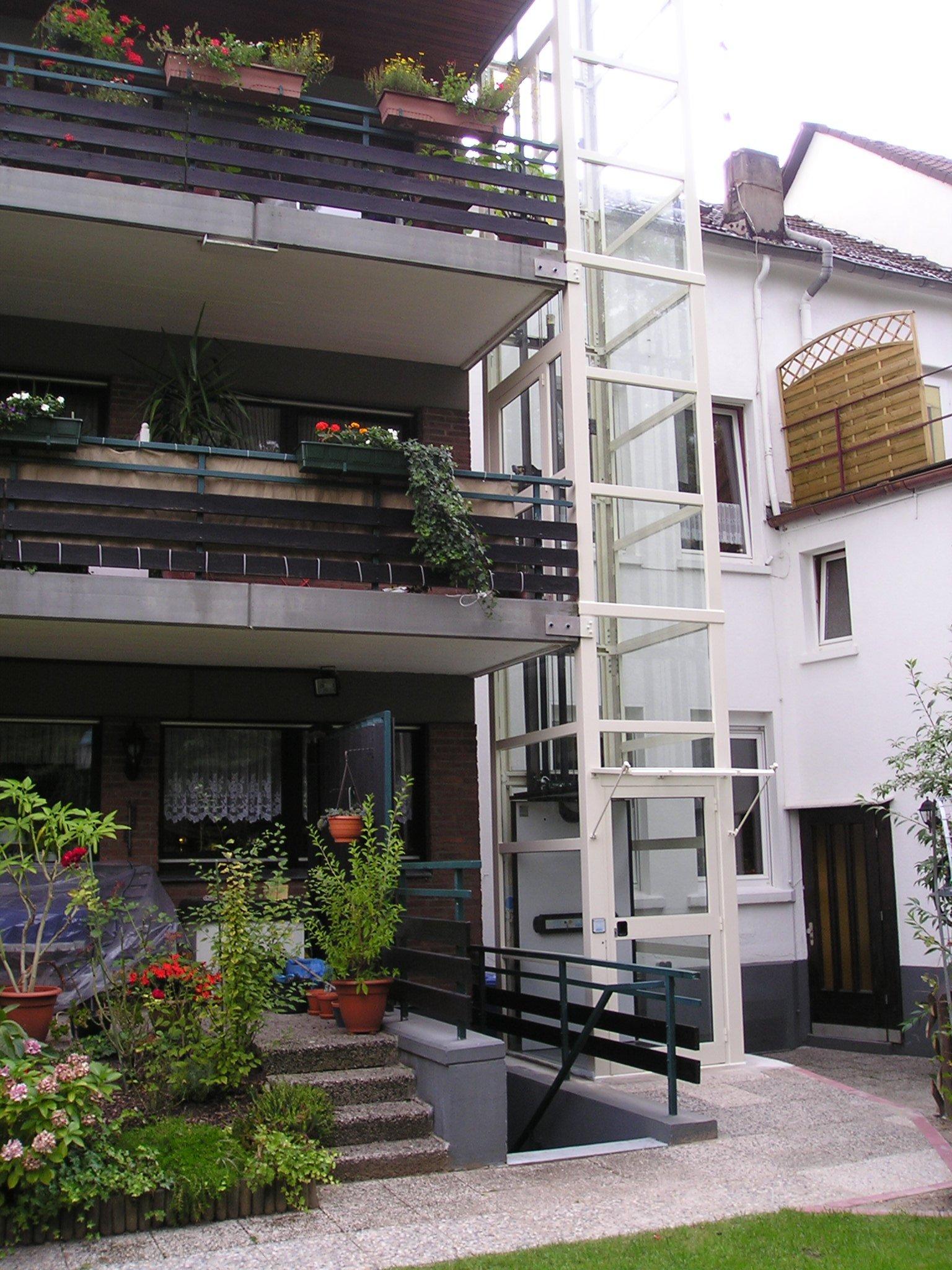 Weißer Außenaufzug aus Glas neben Balkonen
