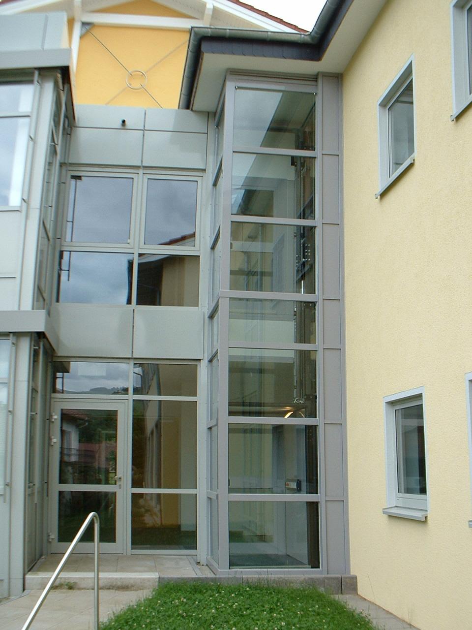 Glasaufzug grau passend zu Eingangsbereich aus Glas