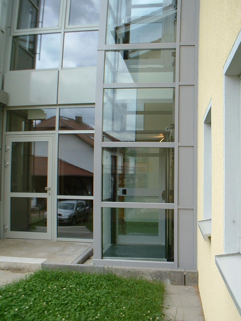 Außenaufzug aus Glas neben Glaseingang