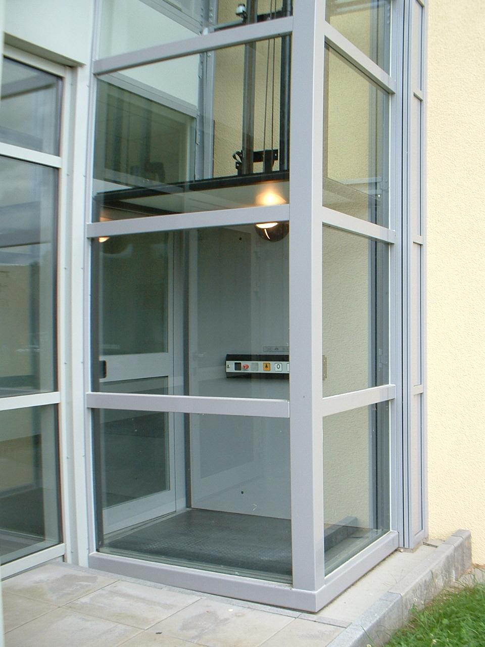 Zugang zum Außenaufzug Glas und weiß