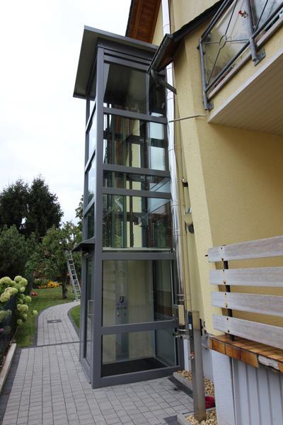 Außenaufzug aus Glas außen an Haus angebaut