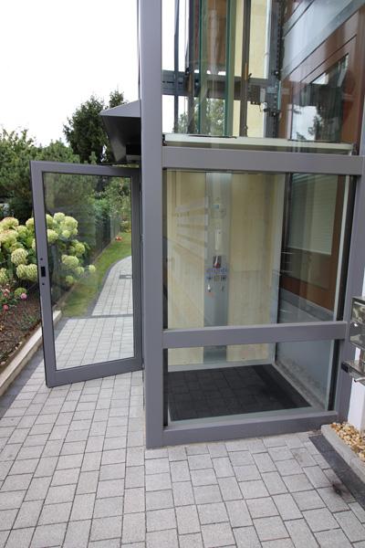 Eingang zu einem Außenaufzug aus Glas vom Gehweg aus
