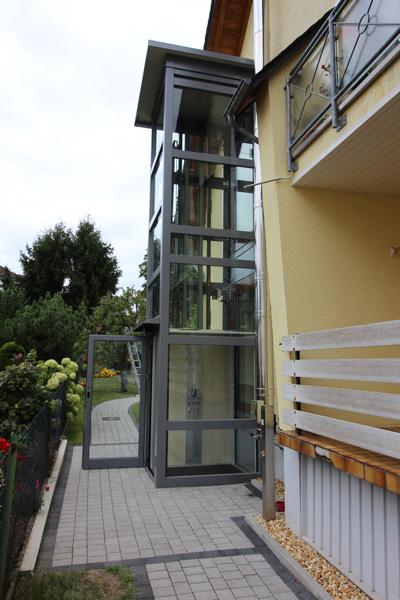 Außenaufzug aus Glas passend eingebaut neben mehrstöckigem Haus