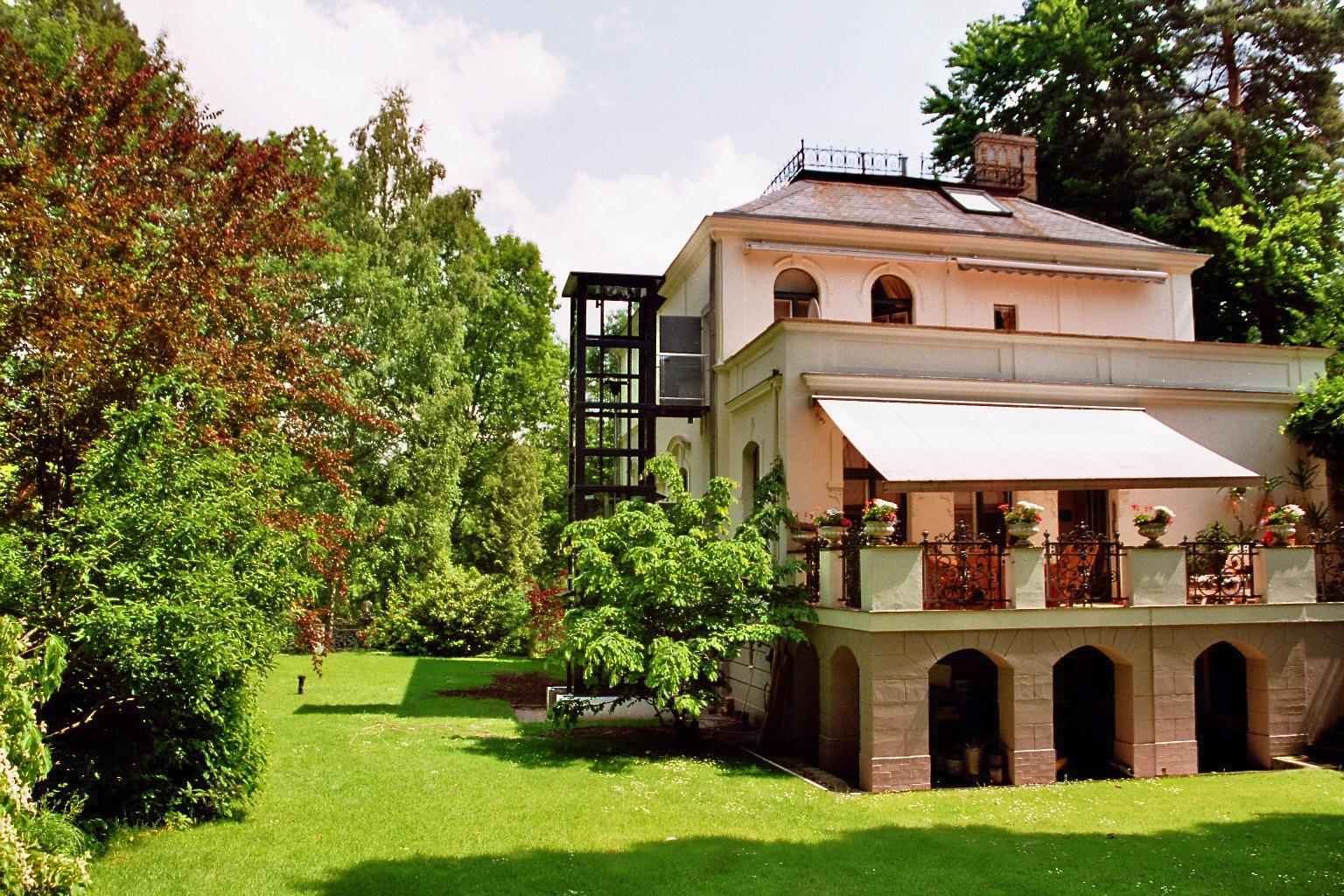 Eine alte stilvolle Villa hat einen Außenaufzug aus Glas bekommen