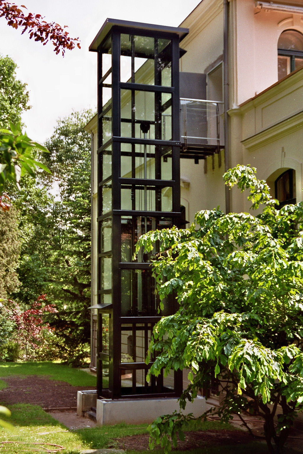 Glasaufzug neben einem Albau im Garten installiert