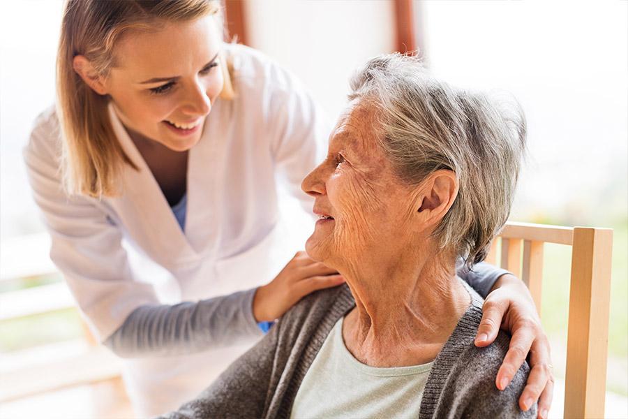 Pflegerin kümmert sich um alte Frau
